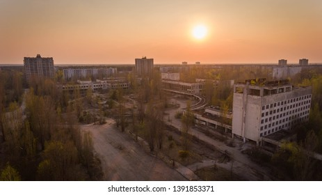 Prypiat, Ukraine, 5th may, 2019. Aerial of a block of ghost houses in Chernobyl with an old parking lot at sunset