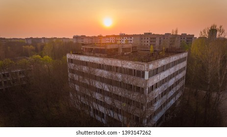 Prypiat, Ukraine, 5th may, 2019. Aerial shot of a dead cubic house with broken windows in Chernobyl at red sunset