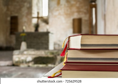 Psalm books in red covers in ancient protestant church. Cross and altar in the background.