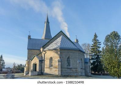 A pseudo-Gothic St. George's Lutheran Church in Jüri, a small village near Tallinn, capital of Estonia. Blue clear December sky, smoke from chimney, few trees on graveyard around religious building.
