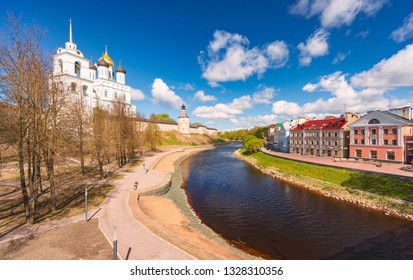 Pskov church and kremlin with blue cloudy sky in background. River in foreground. Church and houses on river sides.