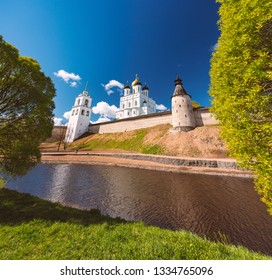 Pskov church and kremlin with blue cloudy sky in background. River in foreground.