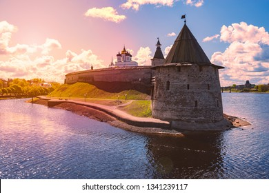 Pskov kremlin tower with blue cloudy sky in background. River in foreground.