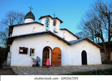 Pskov. Northern Russia. Beautiful scene - Russian orthodox Church of the Intercession and Nativity at the background of evening sky and little girl looks at it.
