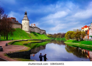 Pskov, Northwest Russia. Beautiful scenic view, great ancient citadel Krom (Kremlin) on the high green bank of Pskova river and few local people fishing and walking at the background of cloudy sky