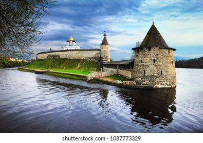 Pskov, Russia. Beautiful scenic view, Trinity Cathedral behind the great wall of ancient citadel Krom (Kremlin) at the junction of the Velikaya and Pskova river at the background of cloudy sky