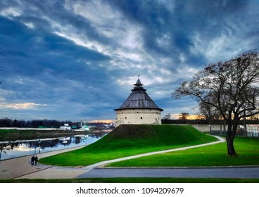 Pskov, Russia. Beautiful scenic view, ancient Pokrovskaya tower with wooden hipped roof, old town wall, Velikaya river, green lawn and walking people at the background of dramatic sky at evening