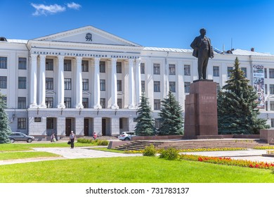 Pskov, Russia - July 11, 2014: Lenin monument from Soviet period stands in front of Pskov State University. Ordinary people walk on square