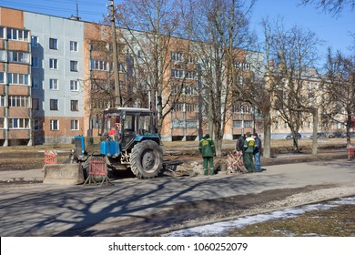 PSKOV, RUSSIA - MARCH 29, 2018: Road repairs site with construction equipment and people watching the work