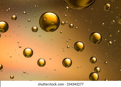 Psychedelic oil and water abstract in gold and brown with a rainbow effect