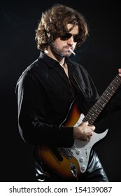 Psychedelic rock guitarist with long brown hair and beard. Dressed in black. Wearing sunglasses.