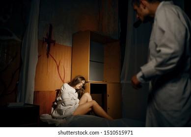 Psychiatrist with torch, patient in strait jacket
