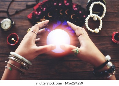 Psychic readings and clairvoyance concept / Crystal ball fortune teller hands and Tarot cards reading divination , with effect filter blur selective focus