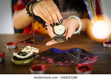 Psychic readings and clairvoyance concept / Crystal ball fortune teller with hands hold retro pocket watch and Tarot cards reading divination