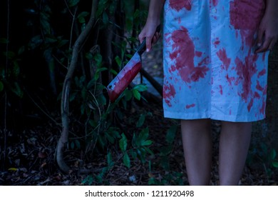 A Psycho ghost holding a bloody knife in the forest.Undas,Obon,El Dia de los Muertos,Halloween,Hungry Ghost,Gai Jatra,Chuseok.