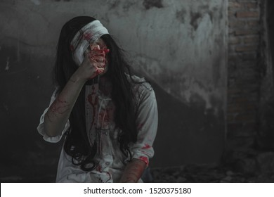 Psycho woman self harming with knife. Zombie girl holding knife with blood. Horror and Scary concept. Thriller Concept.