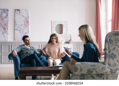 Psychological consultation. Worried couple listening to psychologist during a therapy sitting on a sofa at home.