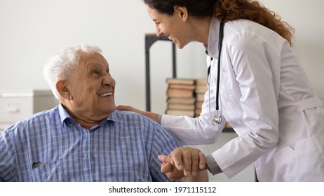 Psychological support. Friendly medical worker caregiver help assist older male with hard diagnosis. Smiling female doctor talk with old man patient express empathy share positive emotions hold hand