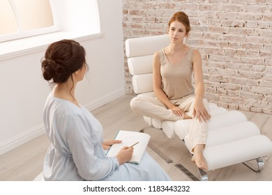 Psychologist having session with her patient in office. Professional psychologist conducting a consultation. Two women communicating indoors. Adult female psychologist working with girl. People in