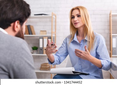 Psychologist having session with her patient in office, giving him advice about his life
