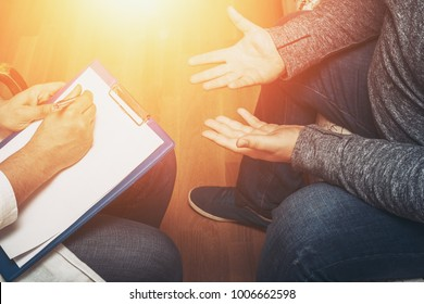 Psychologist listening to her patient and writing notes, mental health and counseling. Psychologist consulting and psychological therapy session concept, toned photo