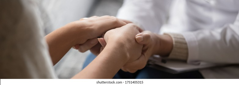 Psychologist in white coat holding hands of woman patient provide professional aid psychological help close up, show support express empathy concept. Horizontal photo banner for website header design