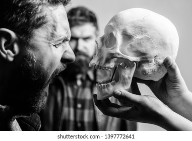 Psychology concept. Human fears and courage. Looking deep into eyes of your fear. Man brutal bearded hipster looking at skull symbol of death. Overcome your fears. Be brave. Focused on breaking fear.