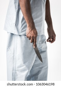 psychosis or Psychiatric patients man wearing patient suit  holding knife on white background