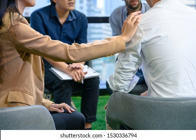 Psychotherapist inquiring about symptoms occurring within mind from patients with mental health problems in hospital. Group psychotherapy for support and helping worried man to change negative mindset