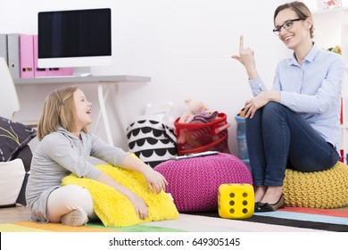 Psychotherapist woman using play activities for teaching young girl to count