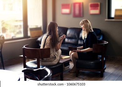 Psycologist consulting woman client indoors. Two women communication and discussion
