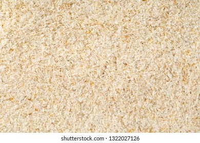 Psyllium husk also called isabgol frame filling texture background flat lay from above. Psyllium husk is fiber derived from the seeds of Plantago ovata plant found in India. Flat lay from above.
