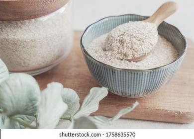 Psyllium husk in wooden spoon and bowl on wooden plate, superfood fiber prebiotic food for gut health