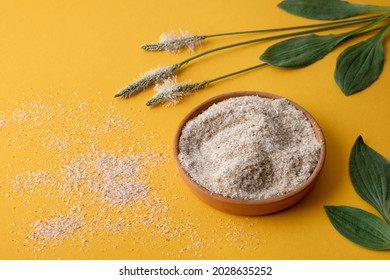 Psyllium, isfagula plant product is the husk of plantain seeds in a plate on a yellow background. Useful dietary supplement, superfood. Top view, horizontal orientation, without people, copy space.
