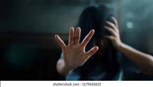 PTSD Mental health concept. Post Traumatic Stress Disorder. The depressed woman sitting alone on the floor and waving refusal to help from people in the dark room background. Film look. Soft focus.