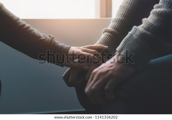 PTSD Mental health concept, Psychologist sitting and touch hand young depressed asian man for encouragement near window with low light environment.Selective focus.