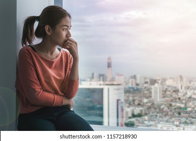 PTSD Mental health concept, Young depressed asian woman sitting near window with low light environment.Selective focus.