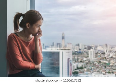 PTSD Mental health concept, Young depressed asian woman sitting alone near window in dark at evening time with low light environment.Selective focus.