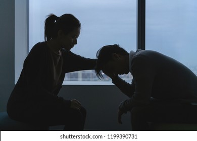PTSD Mental health concept, Young depressed asian man talking with psychologist sitting near window in dark room at evening time with low light environment.Selective focus.