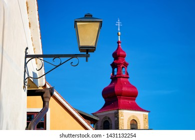 Ptuj City Tower and street lantern in the center of old town in Slovenia. Building architecture in Slovenija. Travel. Blue sky on the background.
