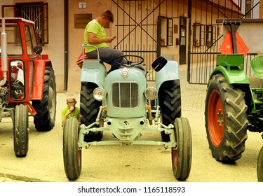 PTUJ, SLOVENIA, May 20 2018: A boy is sitting on the old Eicher Diesel tractor and looking in the mobile phone, while other is eating an ice cream while sitting on the pavement at Ptuj, Slovenia.
