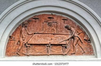 PTUJ, SLOVENIA, May 20 2018: Bas relief scene showing three men playing billiards on the wall of guest house in Ptuj, Slovenia.