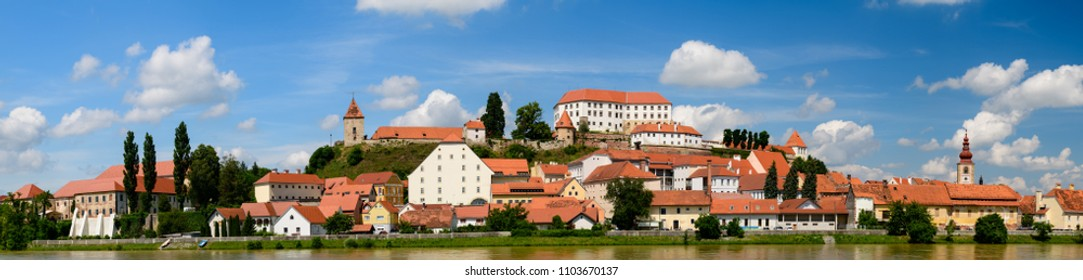 Ptuj, Slovenia, panoramic shot of oldest city in Slovenia with a castle overlooking the old town from a hill and the Drava river beneath, clouds moving across the sky time lapse