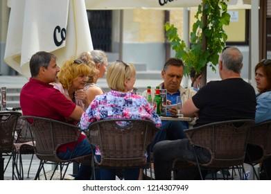 Ptuj,Slovenia/ Slovenia-06.25.2018:Group of people sitting on stools in Ptuj square