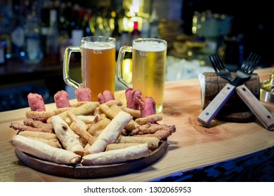 Pub food served with cold beer at bar counter