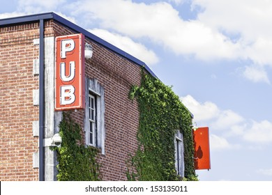 A pub sign located on the side of a brick building.