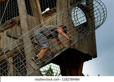 The puberty boy is climbing through a wire tunnel into a wooden shed .The boy climbs in the middle of a wire tunnel.