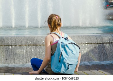 Puberty little girl sitting and look in to water fountain, rest and refreshing after school.Back of child girl with back pack anxiety single and pensive on warm day.