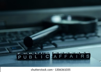 Public Affairs text wooden blocks in laptop background. Business and technology concept