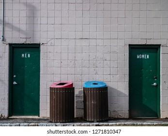 public bathroom doors with pink and blue trash bins
